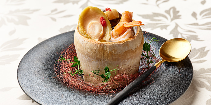Double-boiled Chicken Soup with Abalone, Dried Scallops, Fresh Prawn and Chinese Mushrooms served in Young Coconut from Hai Tien Lo in Pan Pacific Singapore in Promenade, Singapore